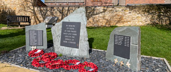 Memorial Green site with three stones and plaques.  The central large stone has a plaque with a general remembrance statement for the fallen. The two smaller stones either side have plaques with a roll call of the parishioners who lost their lives in the